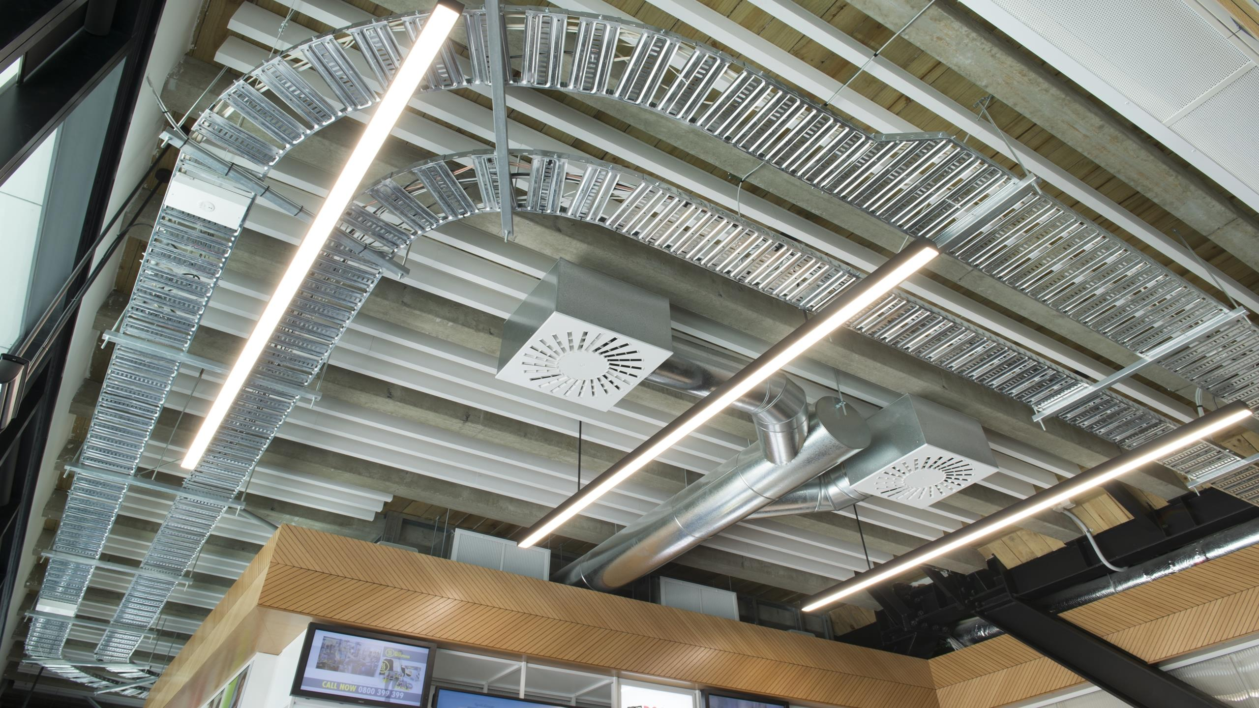Media Works reception area showing white linear Baffle beams installed in exposed conduit ceiling plan